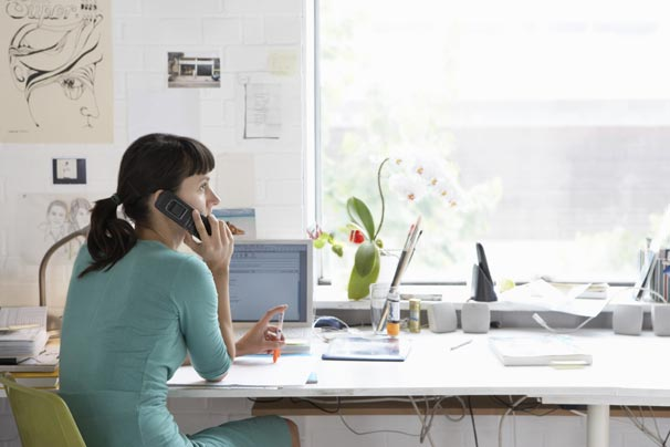 Woman at home desk on phone