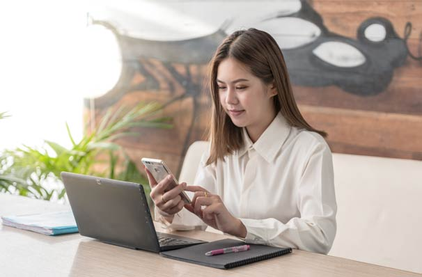 Woman working with phone laptop